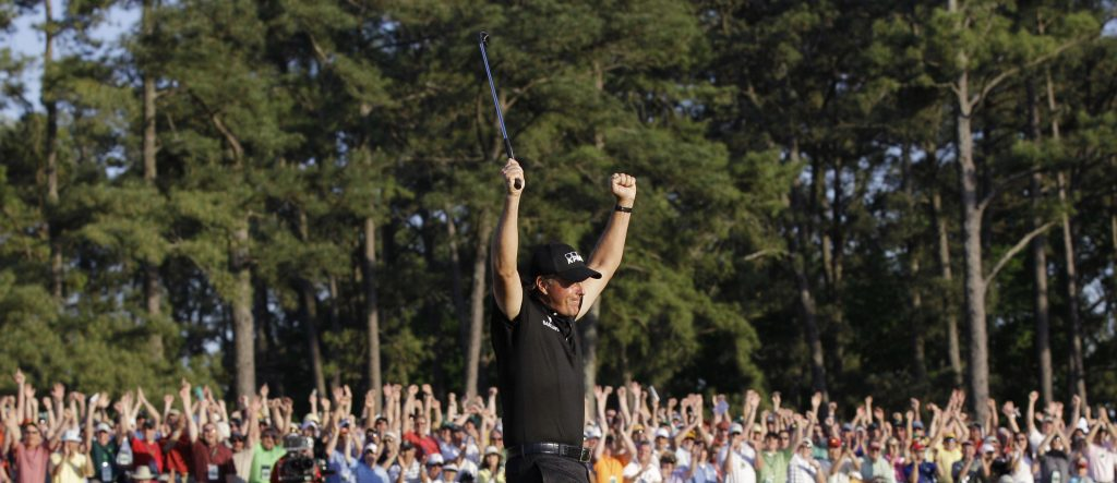 Phil Mickelson celebrates on the 18th green after winning the Masters golf tournament.